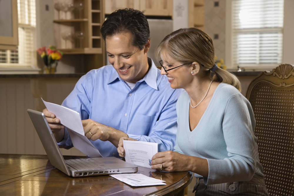 Couple paying bills online with laptop computer at home.