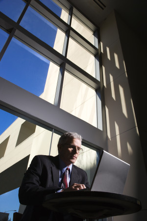 Low angle view of a businessman with a laptop computer in front of large windows. Vertical shot.